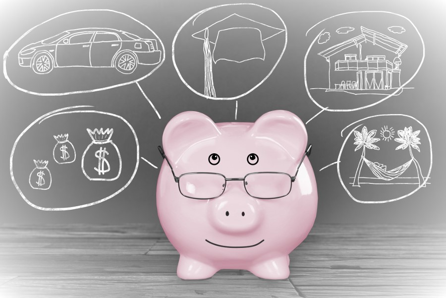 Pink Piggy bank with financial goals on blackboard